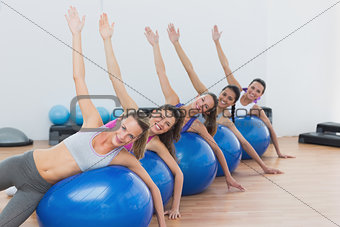 Portrait of class exercising on fitness balls