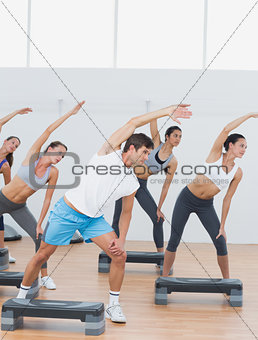 Class doing stretching exercise in fitness studio
