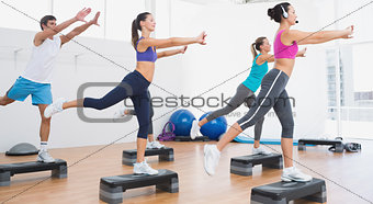 Fitness class performing step aerobics exercise