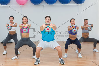 Class and instructor exercising with kettlebells in gym