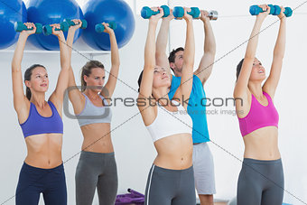 Fitness class exercising with dumbbells