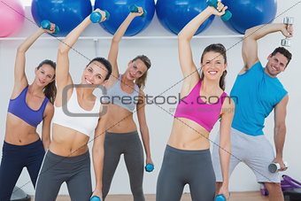 Portrait of fitness class exercising with dumbbells