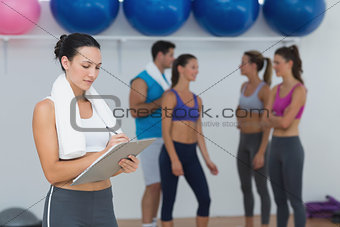 Female trainer writing on clipboard with class in background