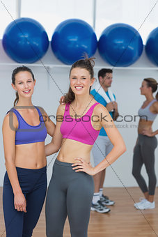 Fit women in sports bra with a couple in background
