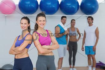 Fit women in sports bra with friends in background