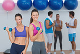 Fit women holding dumbbells with class in background