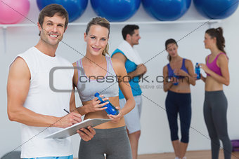 Couple holding clipboard with fitness class in background