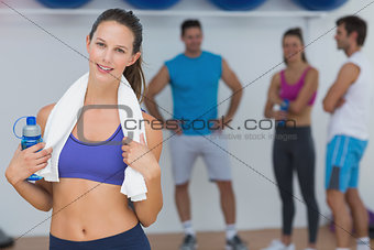 Fit female holding water bottle with fitness class in background