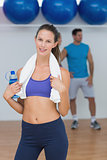 Portrait of a fit female holding water bottle with a man in background at gym