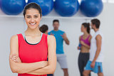 Smiling woman with friends in background at fitness studio