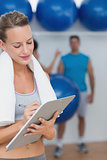 Trainer writing on clipboard with fitness class in background at gym