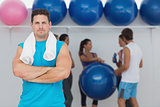 Fit man with friends in background at fitness studio