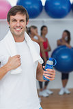 Man holding water bottle with friends in background at fitness studio
