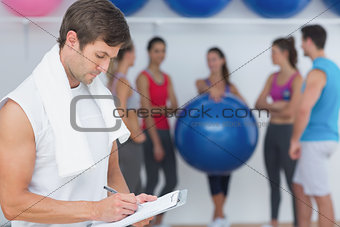 Trainer writing in clipboard with fitness class in background