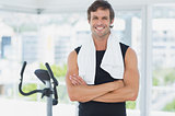 Smiling man standing with arms crossed at spinning class in bright gym