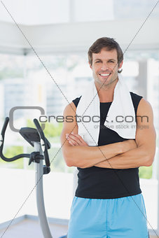 Smiling man with arms crossed at spinning class in bright gym