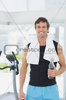 Smiling man holding water bottle at spinning class in bright gym