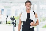 Smiling male trainer with clipboard in bright gym