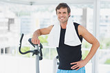 Smiling man standing at spinning class in bright gym