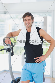 Portrait of a smiling man at spinning class in bright gym
