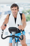 Smiling man working out at spinning class in bright gym