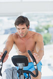 Determined man working out at spinning class in bright gym