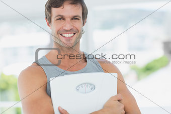 Fit young man with scale in bright exercise room