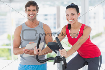 Woman with instructor working out at spinning class in bright gym