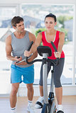 Fit woman with male instructor working out at spinning class