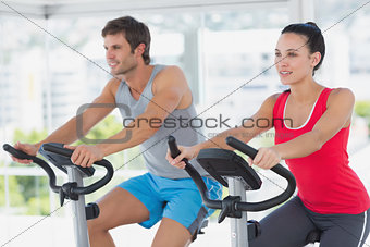 Fit young couple working out at spinning class