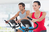 Determined couple working out at spinning class in gym
