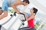 Determined couple working out at spinning class