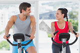 Couple working out at spinning class in bright gym