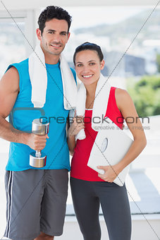 Fit couple with dumbbell and scale in bright exercise room