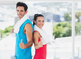 Fit couple gesturing thumbs up in bright exercise room