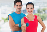 Fit couple with dumbbell in bright exercise room