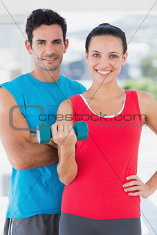Fit couple standing with dumbbell in bright exercise room