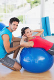 Male trainer helping woman with her exercises