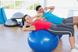 Fit young couple exercising on fitness balls at gym