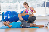 Female trainer helping man with his exercises at gym