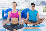 Couple sitting in lotus posture and eyes closed at fitness studio
