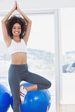Fit smiling woman standing in tree pose at gym
