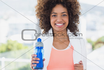 Fit young female holding water bottle at gym