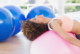 Side view of a fit young woman exercising on fitness ball