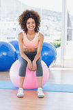 Portrait of a fit woman sitting on fitness ball at gym
