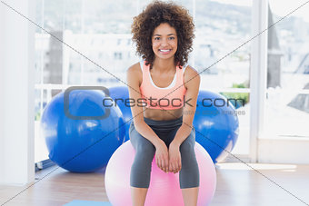 Fit young woman sitting on fitness ball at gym