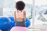 Rear view of a fit woman on fitness ball at gym