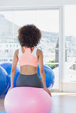 Rear view of a fit woman sitting on fitness ball at gym