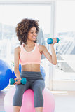 Woman exercising with dumbbells on fitness ball in gym