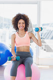 Woman exercising with dumbbells on fitness ball gym